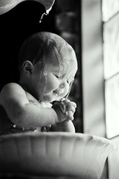 This is a portrait picture of a baby being bathed using a jug and a water basin. This to me is a very 'cute' picture as the baby has his/her hands together and his/her eyes closed when the water is poured over his/her. like a silent prayer