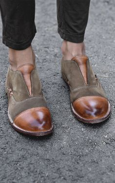 Green and tan BEDSTU slip on loafers, styled with black pants.