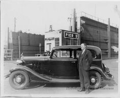 Photograph, ca. 1940 of a man next to a black Chevrolet coupe at Pier 3, Beth Steel, Hoboken, NJ.  (Hoboken Historical Museum)