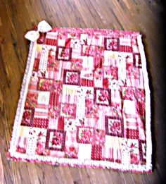 Quilted baby blanket in hues of red pink, and white. Trimmed with a lovely array of ruffled antique white lace and a satiny pink bow in the left corner. Found only here at