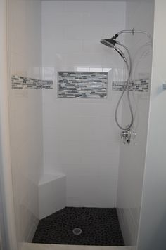Small shower design by Investcove Properties. Large format subway tile w/ marble & glass listello, and river rock shower floor. Custom extra large nook.