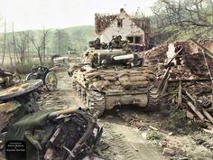 An American M4A1 (76mm) Sherman tank of the 14th Armoured Division moves past a roadside littered with debris from the retreating German forces near, Silz, Germany, 23 March 1945. This tank is fitted with a .30-caliber machine gun instead of the...