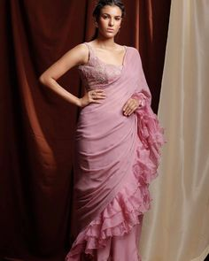 This set features a mauve georgette sari with organza ruffles along the side and hem. It is paired with a wide neck, sleeveless blouse tailored in mauve floral printed georgette and embellished with pearl, sequins & glass beads. Bollywood Saree, Bollywood Fashion, Bridal Wardrobe, Ruffled Feathers, Saree Trends, Simple Sarees, Chiffon Ruffle, Ruffles, Organza Saree