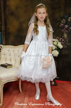 Organza lace first communion dress with three quarter sleeves. Zipper closure with bow tie back. Lace scalloped trim hem. The first communion dress is new for season 2016 and Made in the USA