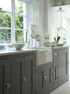 Stunning kitchen with gray kitchen cabinets, polished nickel latches, farmhouse sink, marble counter tops, polished nickel gooseneck bridge faucet, subway tiles backsplash and light gray walls.