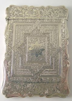 A Victorian silver card case, by A & S, Birmingham 1857, of rectangular form with wavy edge and bright cut Persian-style scroll decoration with engraved central cartouche, monogrammed, weight 52gms, 10cm x 6.5cm in original leather-covered case marked Desprez Jeweler and Silversmith, 30 Park Street, Bristol