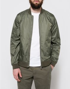 From Norse Projects, a lightweight water-resistant jacket in Dried Olive.  Features bomber neckline, ribbed neckline, full length sleeves, ribbed cuffs, full zipper front, vertical front pockets, ribbed hem, fully lined and classic fit.  •Lightweight w