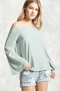 A crepe woven top featuring an elasticized off-the-shoulder neckline, long bell sleeves, and a flowy silhouette.