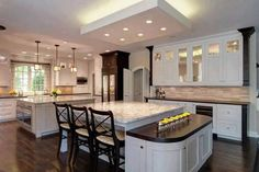 Massive open design kitchen holds two immense, marble topped islands and serving platform. Background island holds a pair of ovens beneath its expanse of countertop. Kitchen by Drury Design. Kitchen Interior, New Kitchen, Home Interior Design, Kitchen Decor, Square Kitchen, Interior Decorating, Luxury Kitchen Design, Luxury Kitchens, Home Kitchens