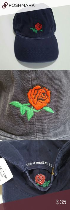 """Brandy Melville Rose Hat Sold Out Brandy Melville navy blue baseball cap hat Katherine style six-panel baseball cap with deep red rose and green leaves and stem embroidery sewn on the front. Adjustable in the back, exposed stitching on  100% cotton 3"""" brim length, 8.5"""" diameter. Brand new unused and unworn with tags still attached. No longer in stores and great with your favorite shirt and jeans. Other great Brandy Melville and accessories in my closet. No trades, no lowest. Brandy Melville…"""