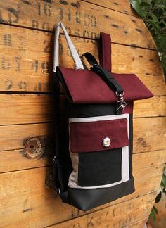Black & burgundy rolltop rucksack made from various textiles and a beer cap as a decorative button