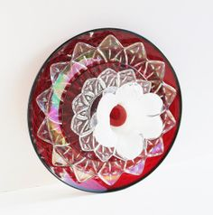 """""""Loves Blossom"""" by TheBlueRam. The center is a white Murano glass candle holder, surrounded by iridescent petal-shaped plates and ruby red glass. Glass Garden Flowers, Glass Plate Flowers, Glass Garden Art, Flower Plates, Glass Art, Garden Stones, Boho Gypsy, Indoor Outdoor, Upcycled Vintage"""