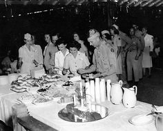 A line of servicemen and women get food from a buffet while attending a dance in Guam in late 1945. Notice the shortened sleeves of summer Off-Duty dresses worn by Army Nurses ~