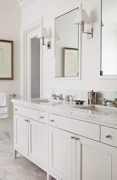 Chic master bath features a cream double vanity topped with white marble fitted with his and her sinks under framed inset medicine cabinets illuminated by polished nickel sconces alongside a marble geometric floor, Walker Zanger Wilshire Field Pattern Tiles.