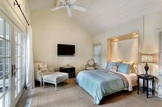 Master bedroom with a king size bed, flat screen tv, and two beautiful french doors that open out onto the patio.