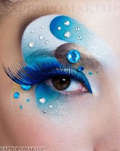 Creative blue and white swirled eye shadow with blue lashes and gem accents by MUA Maria Lihacheva.