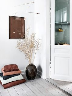Scandinavian space with white-washed wood floors,  a large black vase, and simple art