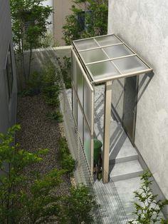 勝手口付近に屋根を設けて、ごみ置き場などに。限られたスペースでも使い勝手はいい。隣家からのプライバシー確保のために目隠しパネルも設置。undefined[独立テラス屋根 エフルージュグラン ZERO 標準柱 フラット型 H2 トーメイマット/前面パネル] YKK AP http://www.ykkap.co.jp/
