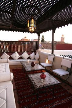 A nice Moroccan terrace overlooking the koutoubia in Marrakesh. Ceramic tiled tables, hand embroidered cushions and a beautiful Moroccan kilim rug to tie it all together! #Moroccan #Terrace #Embroideries #Kilim.