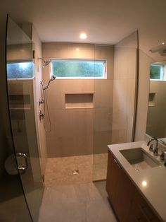Glass shower doors allow this #bathroom's natural light to shine through.