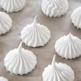 Bake for 60 to 90 minutes.  Depending on the size of your meringue, bake for about 60 minutes, or until the outside is crisp and the inside is dry yet chewy. They should feel light and hollow. When done, the meringue should easily peel off the parchment paper. Turn the oven off, crack the door open, and let the meringue cool completely in the oven.