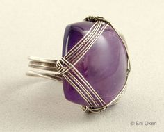 This lesson teaches how to create a ring using a square or rectangular cushion-shaped cabochon. The woven wire on top of the cab creates a simple, but very elegant woven pattern over the stone.  Format: Downloadable PDF Document  Level: Intermediate  Tools and Materials:  8 18 ga round soft or half hard wire ¾ by ¾ square or rectangular cushion-shaped cabochon 3 feet 28ga soft wire Ring mandrel Round nose pliers Flush wire cutter Metallic hammer Metallic anvil or block masking tape  Pages…