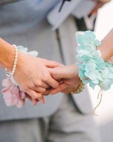 Instead of carrying bouquets, brides Courtenay and Larrison wore wristlets of dyed orchids.