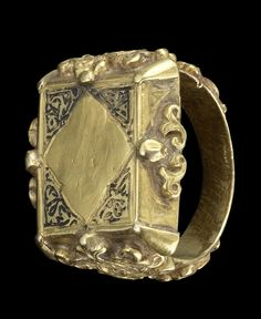 A Seljuk niello and gold Ring   Persia, 12th/ 13th Century  the rectangular bezel with a blank quatrefoil cartouche, the spandrels in niello with arabesque designs, the shank and band with applied floral interlace and further details in niello