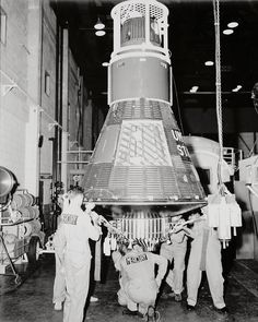 """Personnel in Hangar S at Cape Canaveral, Florida prepare Wally Schirra's Mercury 8 capsule nicknamed """"Sigma 7"""" for delivery to the launch pad to be mated to the Atlas launch vehicle."""