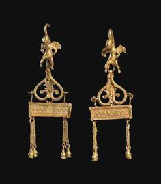 A PAIR OF GREEK GOLD EARRINGS   HELLENISTIC PERIOD, CIRCA 3RD-1ST CENTURY B.C.   Each composed of a seated figure of nude Eros, head bent forwards looking down, hands held slightly in front, wings outspread behind, earring hoop attached at back of head,