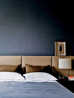 navy bedroom with camel headboard