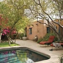 The pool, with its blue-green bottom, was designed years ago by feel like you were swimming in a canal. Sweet acacia and ironwood trees provide a canopy of shade in the west-facing yard.