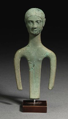 AN ETRUSCAN BRONZE FIGURE OF A YOUTH   circa 350-300 b.c.   With a large head with incised center-parted hair combed in front of the prominent ears, the youthful face with large almond-shaped eyes, long straight nose and small mouth, the long neck flattening into abstracted slab-like arms and an elongated torso with small modelled nipples