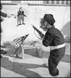 https://flic.kr/p/MFnfWF | Ο Ντούτσε παιχνίδι. | Ένα μικρό αγόρι (Γρηγόρης Μαυρομάττης) με τη στολή της ΕΟΝ (Εθνική Οργάνωση Νέων) σημαδεύει τη φιγούρα του Μουσολίνι (Αθήνα 1940). Φωτογραφία: Βούλα Παπαϊωάννου/Αρχείο Μουσείου Μπενάκη.