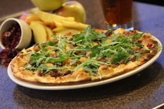 Carmelized Onions, cranberry and roasted apple pizza on our thin homemade pizza crust topped with baby arugula and fresh Parmesan cheese.
