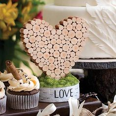 "A great wedding reception table centerpiece would be this sculpted log in the shape of a heart. Made of resin and formed from sculpted stacked logs set in a birchwood-style base topped with moss and it has the word ""LOVE"" in black."