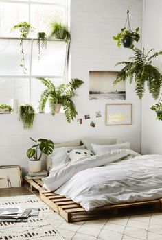 White bedroom with lots of plants and a floor bed. #minimal #plants #bedroomdesign #minimaldecor