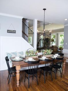 The new dining area of the Dansby home is open and spacious. Some key elements are the wood floors, new chandelier, center pieces, and dining table, as seen on Fixer Upper. (after)