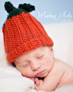 Newborn baby in hand-knit pumpkin hat