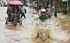 Commuters travel through a flooded street after heavy rains in Guwahati