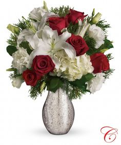 "Christmas Kiss. White hydrangea, red roses, white lilies with flat cedar. Delivered in Teleflora's silver mercury glass royal vase. Approximately 14 1/2"" W x 17"" H."