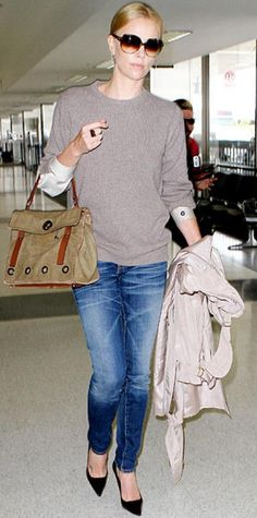 Look of the Day › September 11, 2010 WHAT SHE WORE Theron arrived at LAX in skinny jeans topped by a gray crewneck; she accessorized with a khaki satchel, pointy-toe black pumps and oversize shades.