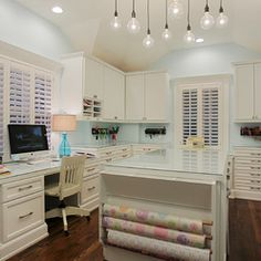 multi-height work area: computer desk, sewing station, crafting/cutting island. white cabinets. glass counters.