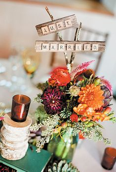 wedding centerpiece of echinaceas, artichokes, dahlias, ranunculuses, freesias, and seeded eucalyptus, with a sign made from scrabble tiles