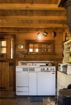 Vintage cabin kitchen with a combination range, oven, broiler, refrigerator and sink, probably from the fifties.