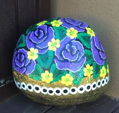Flowers painted on a rock by Linda Hallett.
