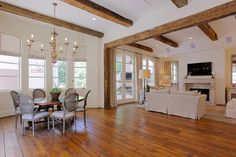 large breakfast room and family room - antique wood beams across the ceiling and the entry between the two rooms is finished with the same antique beams.  A wall of windows include two casement windows.