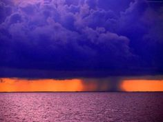 WOW!  deep blue storm clouds..orange sky.....with dark rain fall..and purple ocean.....