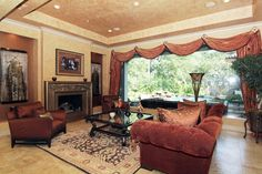 Living room off the entry and dining area in this great open plan. Huge window views the patio, pool and rock waterfall, stone flooring, faux painted walls and ceiling. Custom drapes with swag valance.