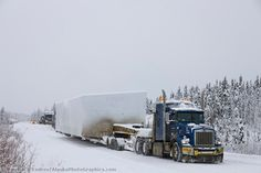 Semi tractor trailer hauls oversize load up the James Dalton Highway in snowy winter road conditions. Push cars assist the main load vehicle.